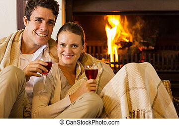 young couple drinking red wine by fireplace