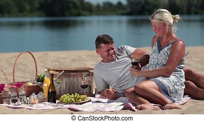 Young couple drinking red wine on picnic