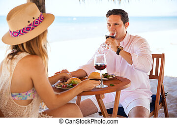 Young couple drinking wine at the beach