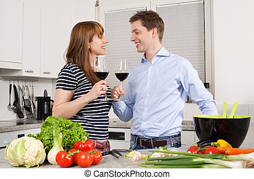 Young couple drinking wine in the kitchen