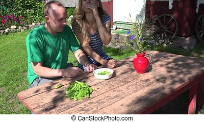 young couple eat green hulled peas in country background. 4K
