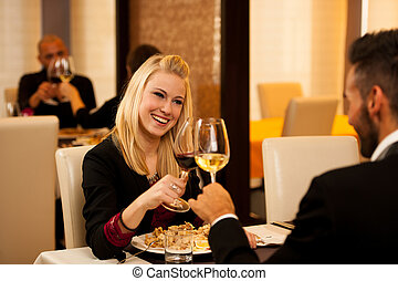 Young couple eat sea food dinner at restaurant and drink...
