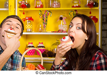 Young Couple Eating Cake at the Cafe