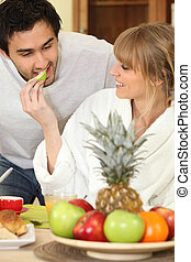 Young couple eating fruit at breakfast