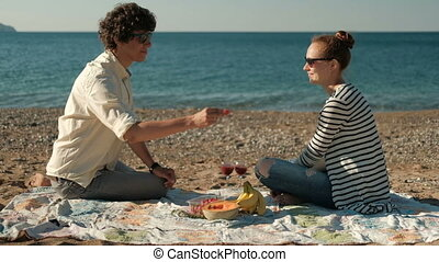 Young couple eating fruit sitting on beach on summer day.