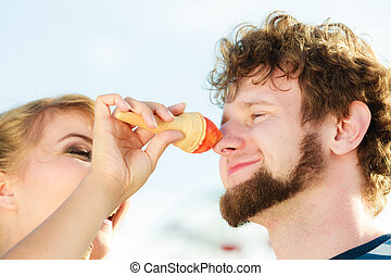 young couple eating ice cream outdoor