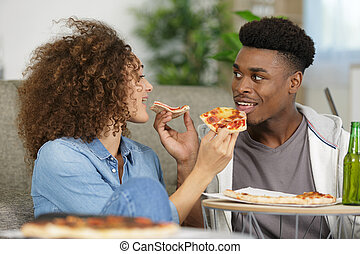 young couple eating pizza on sofa at home