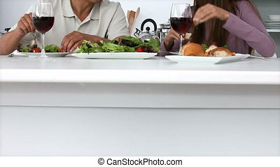 Young couple eating salad with red wine at lunch