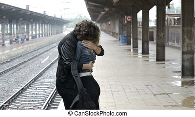 Young couple embracing and saying goodbye before boyfriend...
