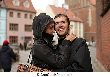 Young couple embracing in an old european town square.