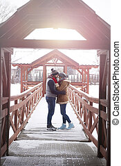 Young couple embracing on winter pier