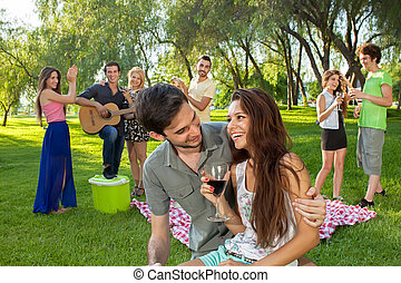 Young couple enjoying a picnic with friends
