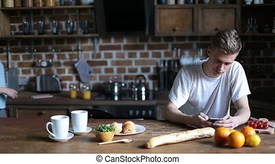 Young couple enjoying breakfast in kitchen