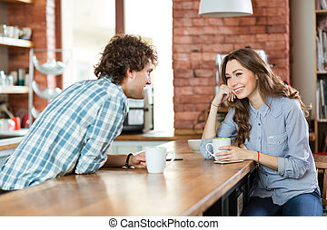 Young couple enjoying coffee in cafeteria