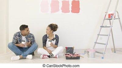 Young couple enjoying coffee while renovating