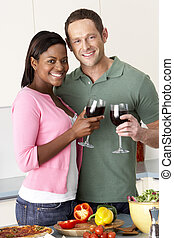Young Couple Enjoying Glass Of Wine In Kitchen