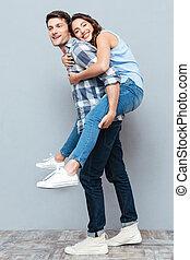 Young couple enjoying piggyback ride over gray background