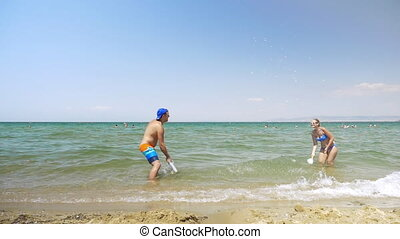 Young couple enjoying ping pong game in the sea