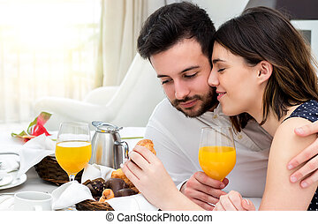 Young couple enjoying room service in suite.
