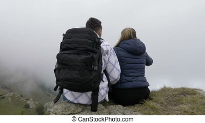 Young couple enjoying the mountain excursion sitting on high...