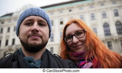 Young couple european beard man and red hair female makes a selfie in Vienna, Austria, rainy autumn