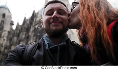 Young couple european beard man and red hair female makes a selfie near Stephansplatz in Vienna, Austria, rainy autumn