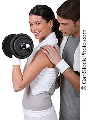 Young couple exercising with a dumbbell