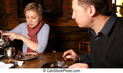Young couple expressively chatting in a cafe
