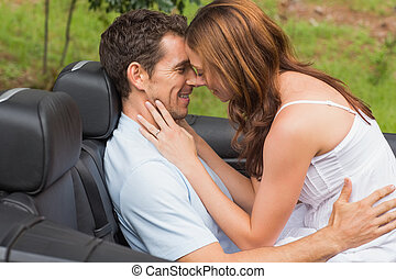 Young couple feeling romantic in back seat of convertible in...