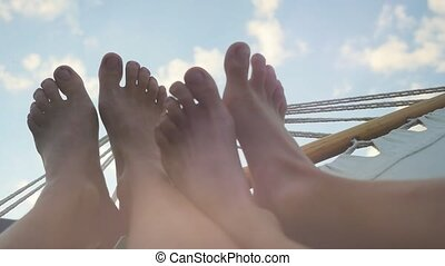 Young couple feet rest in hammock on the sky background in slwomotion. 1920x1080