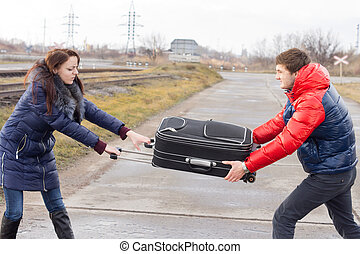 Young couple fighting over a suitcase