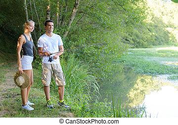 young couple fishing on lake