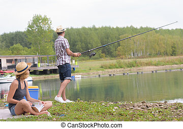 young couple fishing on the banks of the pond