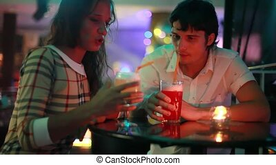 Young couple flirt on date after having drinks at night club bar during party
