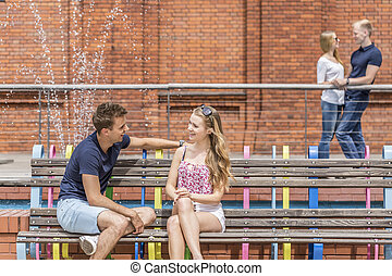 Young couple flirting on a bench
