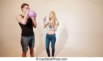 Young couple fooling like children with baloons