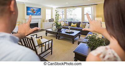 Young Couple Framing Their Hands of Beautiful Home Interior Living Room.