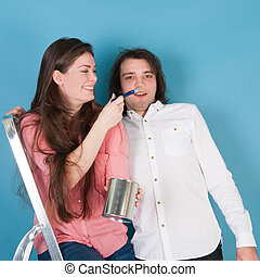 Young couple fun while painting house
