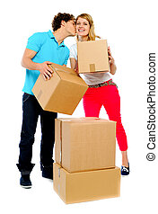 Loving couple rearranging cartons. Guy kissing his girl on cheeks too