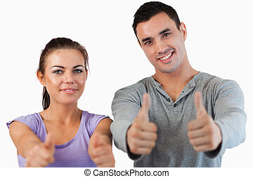 Young couple giving thumbs up against a white background