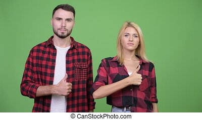Young couple giving thumbs up together - Studio shot of...