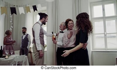 Young couple greeting parents or grandparents on a indoor...