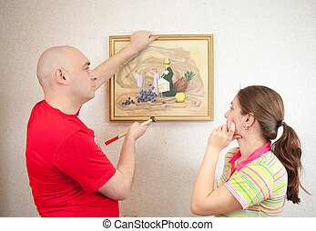 Young couple hanging art picture on wall at