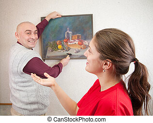 Young couple hanging art picture on wall at. Focus on girl