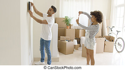 Young couple hanging pictures in their new home aligning it...