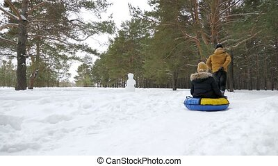 Man is rolling woman on tubing by snow in winter park, back...