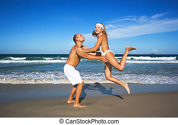 Young couple have a fun time on the beach