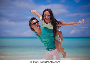 Young couple have fun on white sandy beach