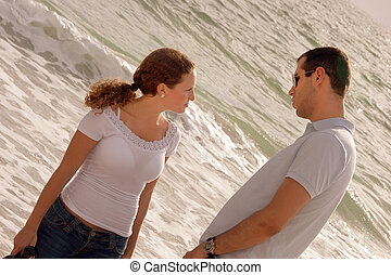 young couple having a serious talk at that oceanside