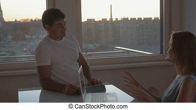 Young couple having a vivid talk using electronics